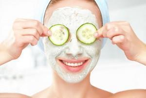 Woman puts cucumbers on eyes while wearing facial mask