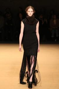Model walks runway with fringe skirt