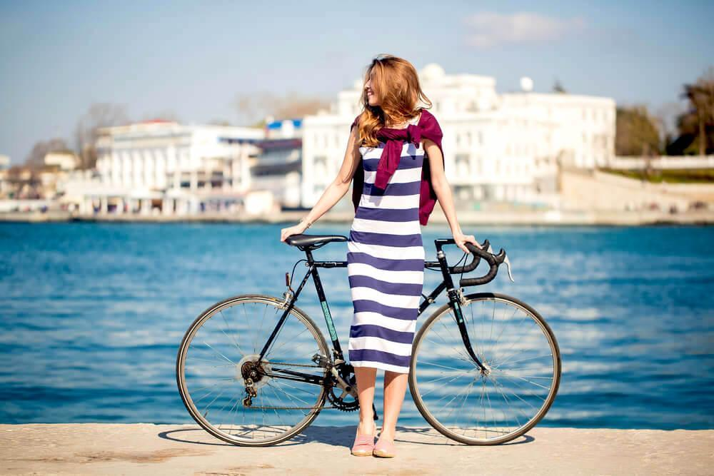 woman in blue-striped dress with bicycle
