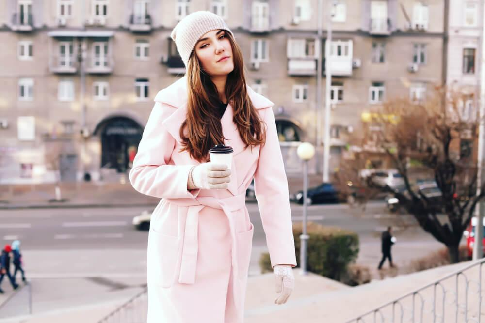 woman in pale pink coat with coffee cup