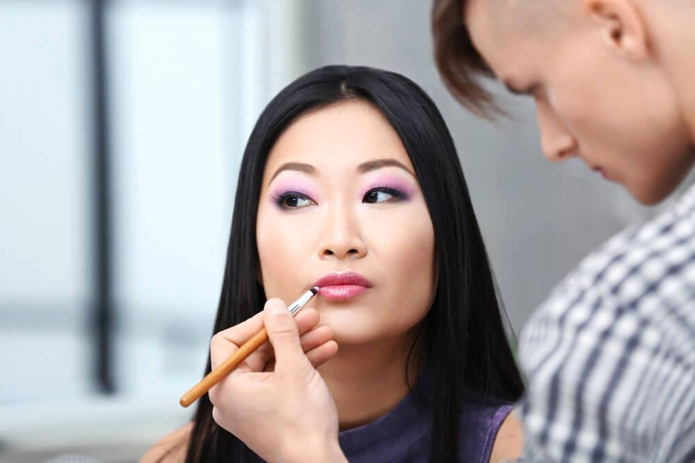 Makeup artist applying lipstick on woman