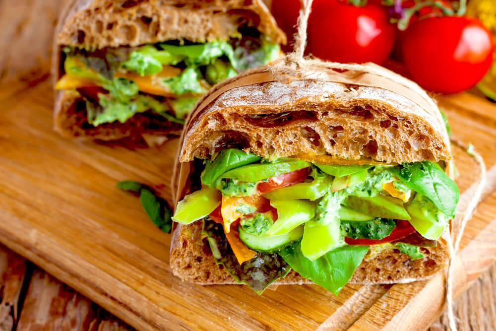Thick veggie sandwich with multigrain bread, on rustic chopping board