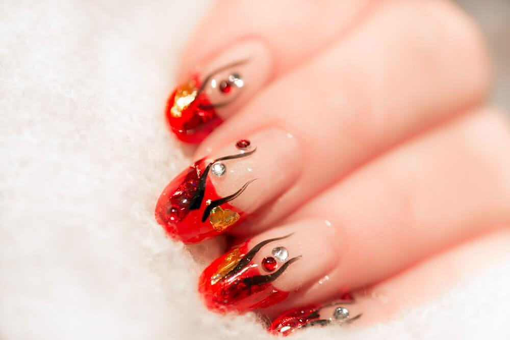 Clear nail art with red accents and design