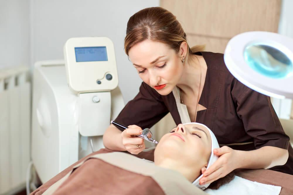 Cosmetologist working on patient's face