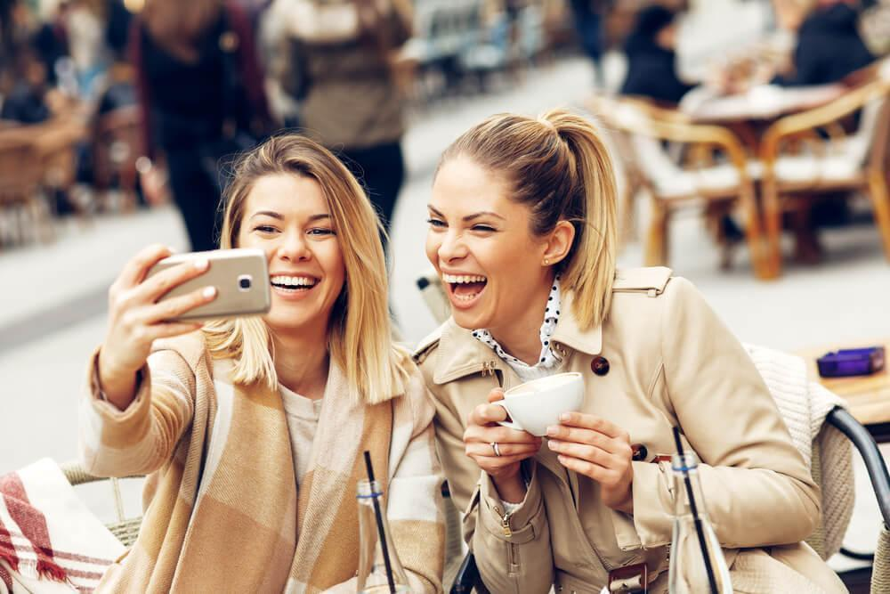 Friends taking a selfie over coffee