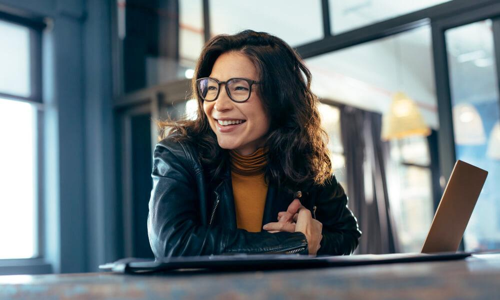 Smiling woman at a desk with her laptop