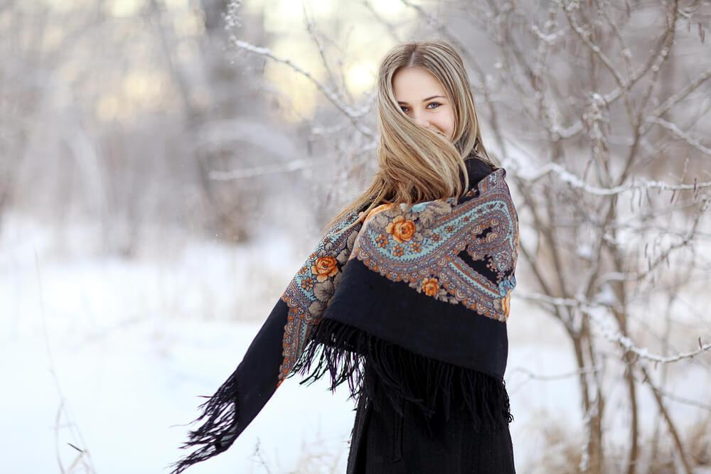 Woman wrapping herself in winter with a long scarf