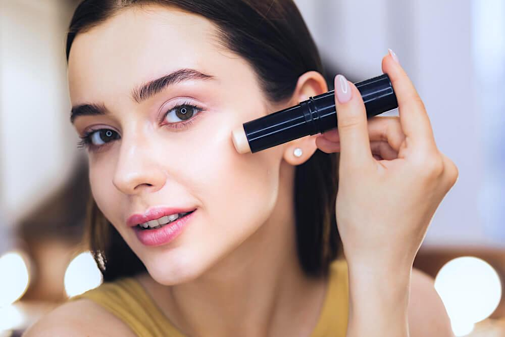 Woman using concealer stick