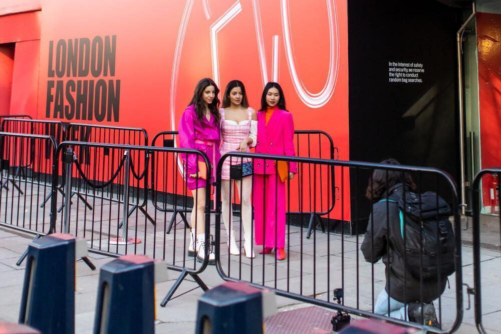 LONDON - FEBRUARY 15, 2019: Stylish ladies wearing pink clothes posing for photographer in front of 180 The Strand for London Fashion Week 2019.