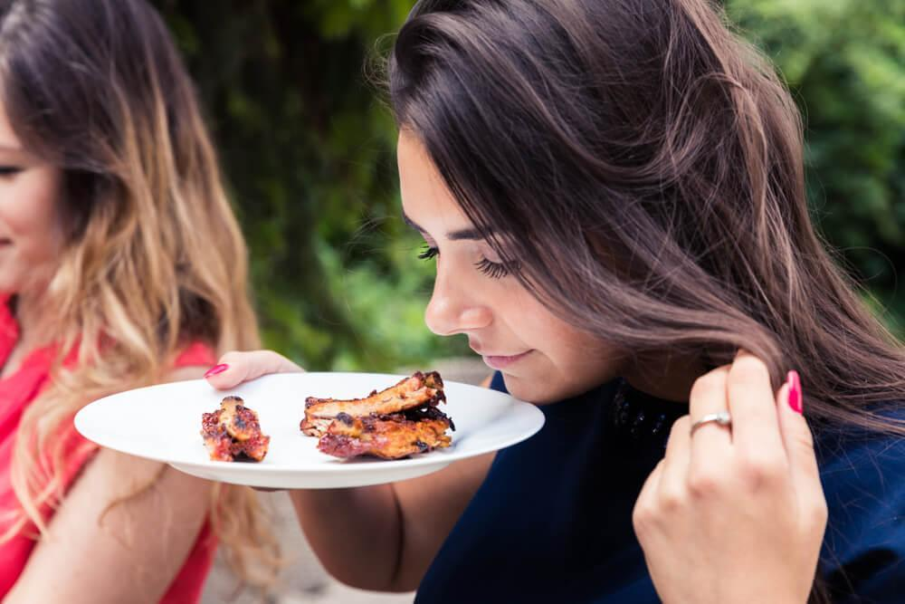 Woman sniffing beef ribs on her plate