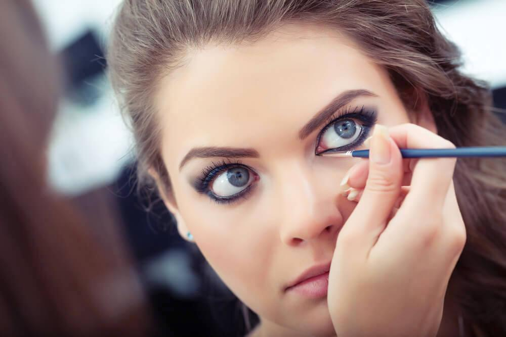 Makeup artist applying white eyeliner on model's eyes