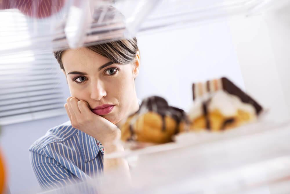 Woman looking longingly at donuts in the fridge