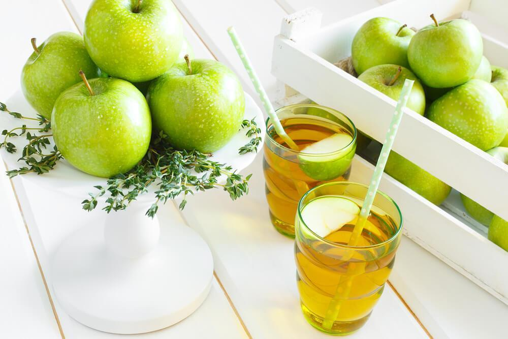Two glasses of apple juice, with whole green apples