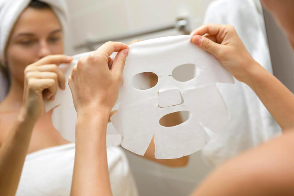 Woman applying sheet mask in bathroom