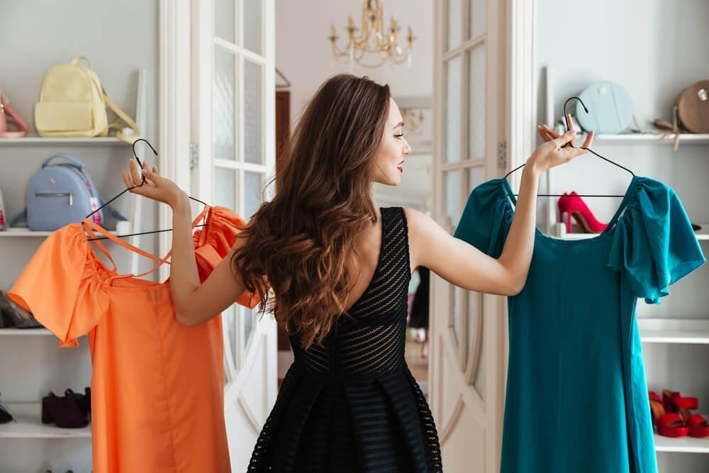 Woman in clothes shop choosing between two dresses