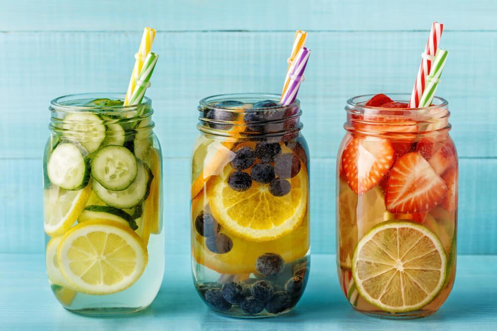 Three mason jars with fruit infused water and straws