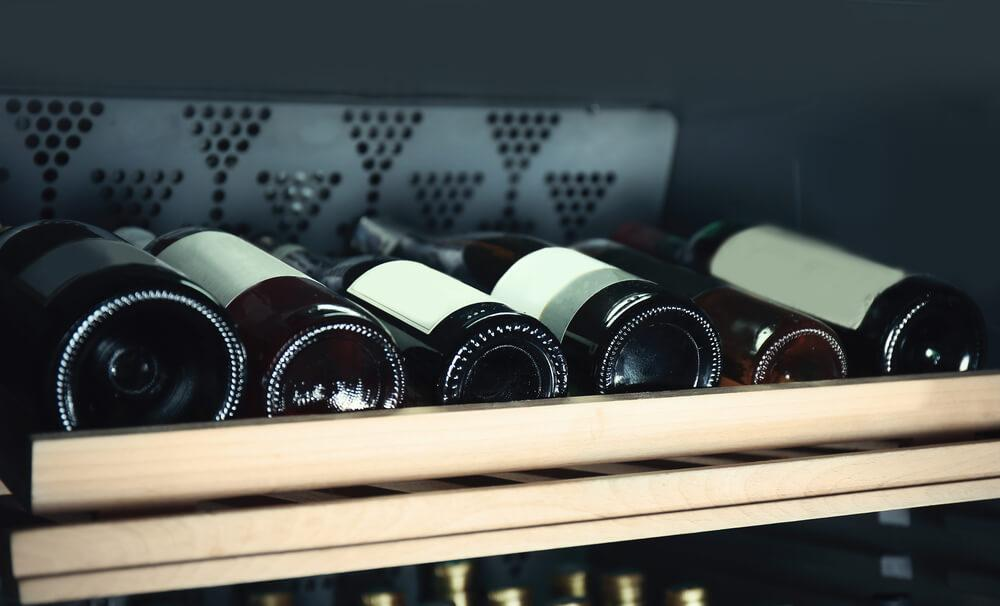 A fridge shelf with bottles of wine