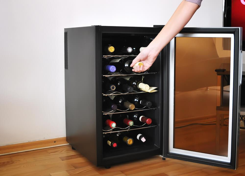 Someone taking a bottle of wine from a wine fridge