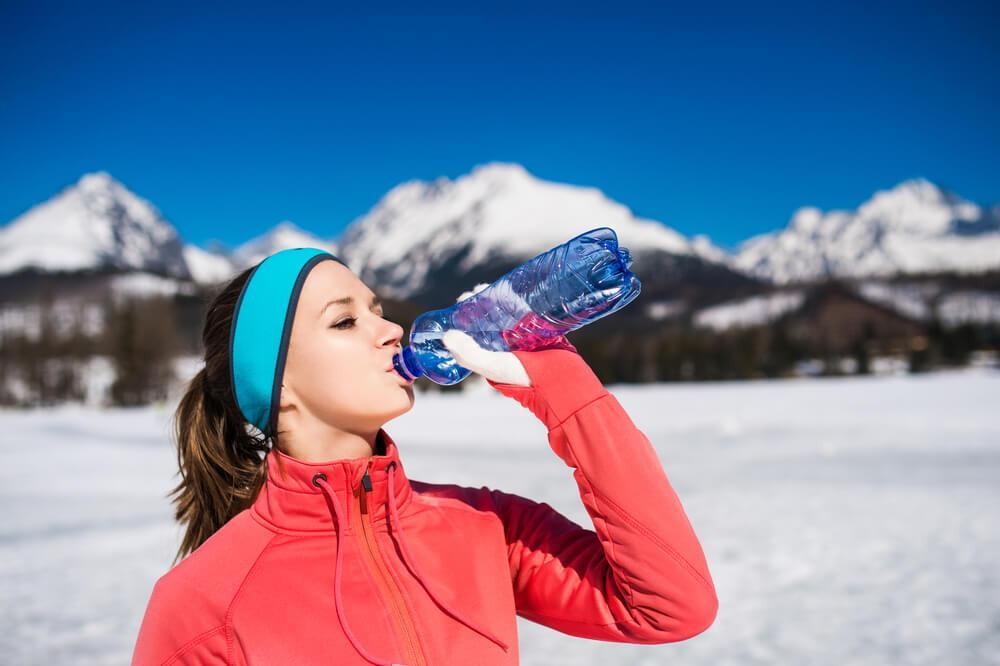 Woman drinking water in snow
