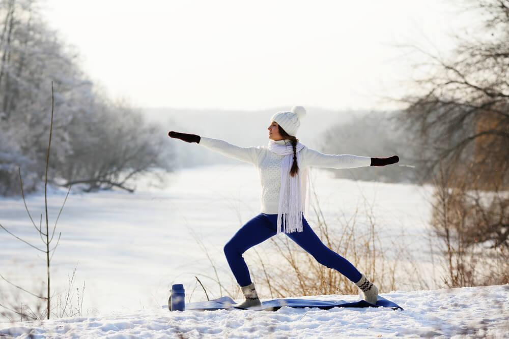 Woman doing yoga in the snow