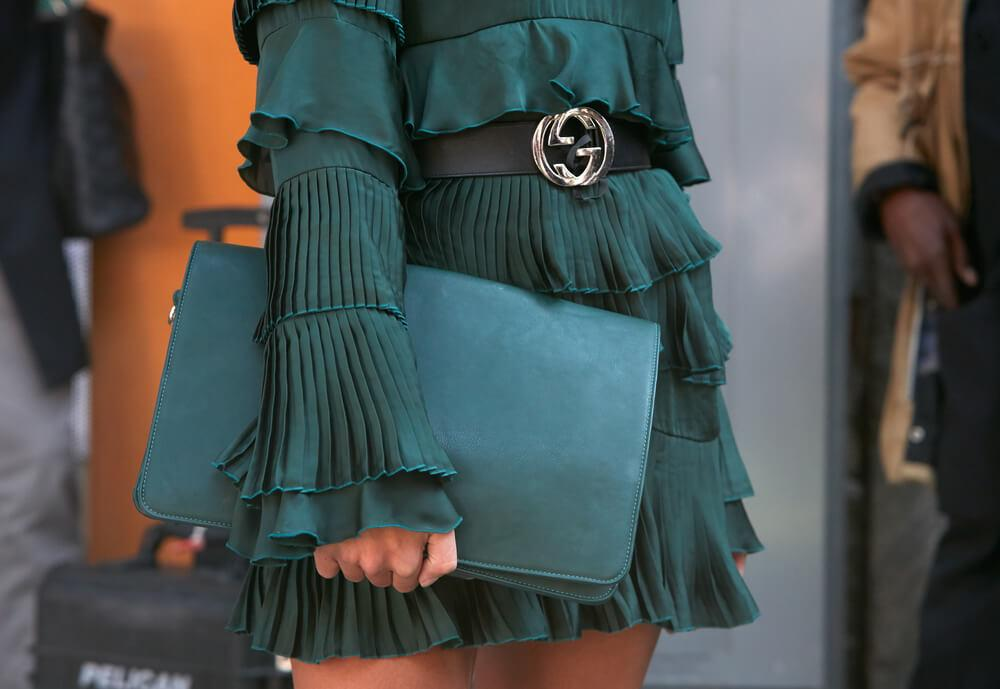 Close-up view of green dress and purse