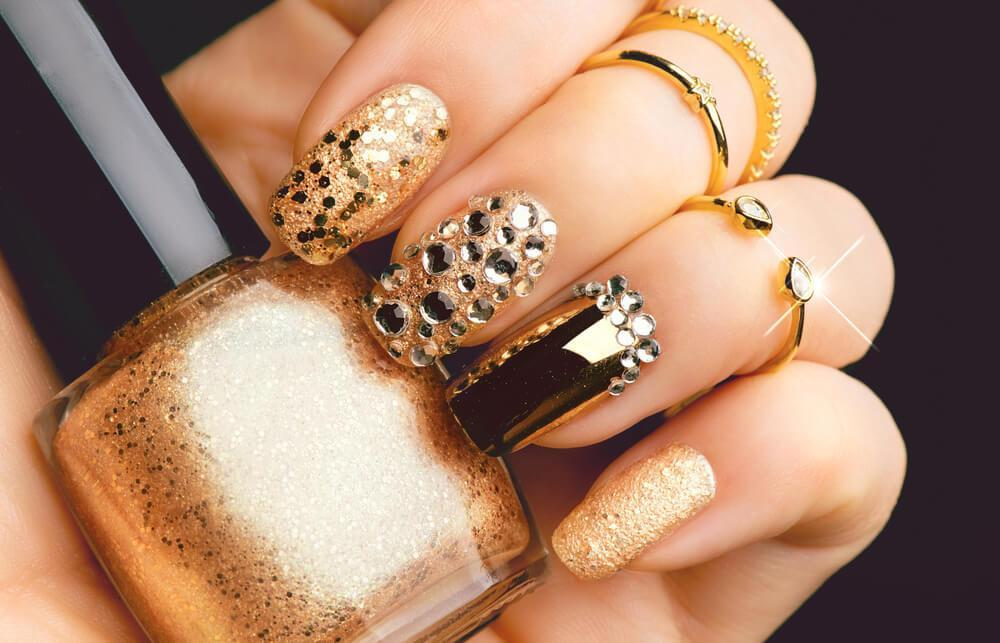 Bejeweled nails holding nail polish bottle