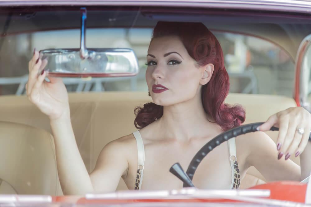 Retro girl with makeup on in car
