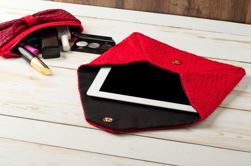 Red purse with tablet and makeup