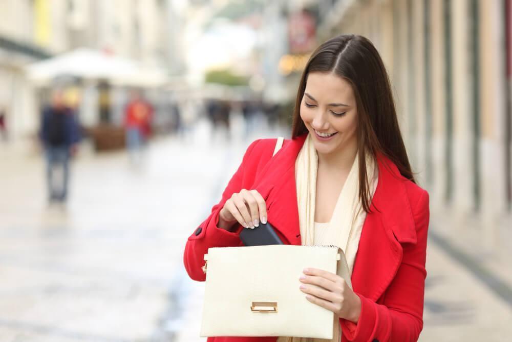 Woman looking into handbag on street