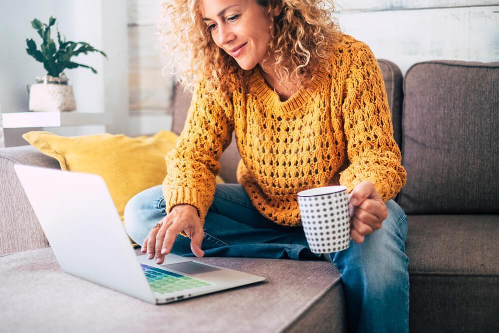 Woman holding mug looking at laptop
