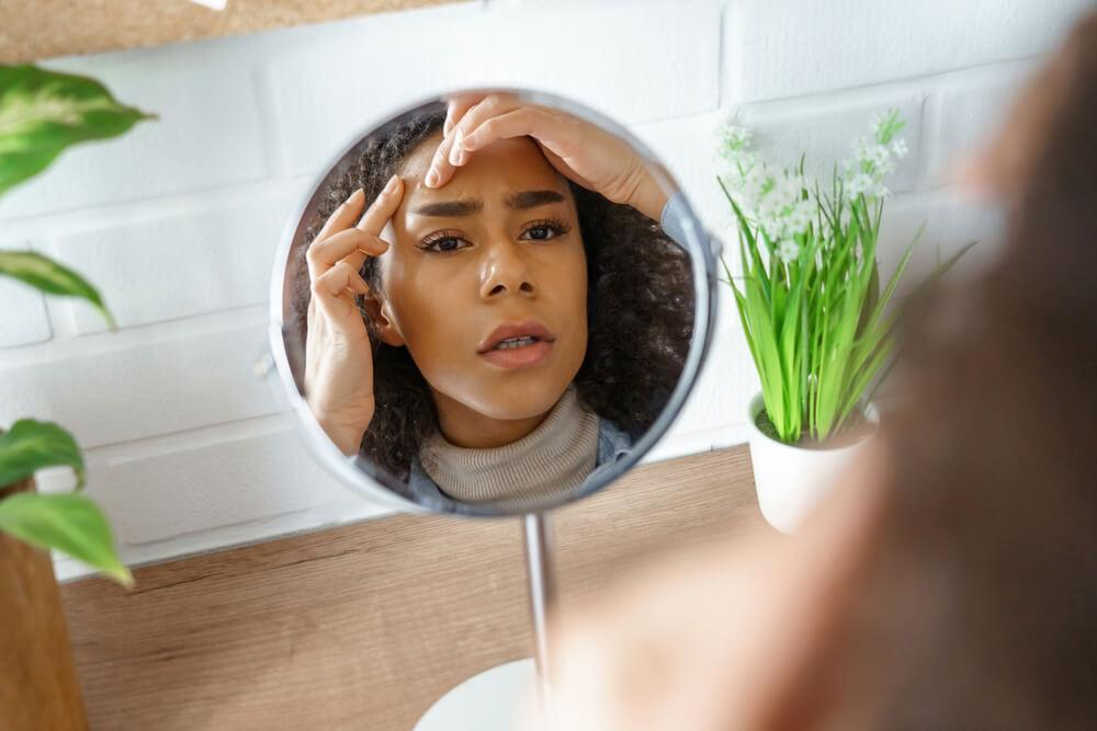 Woman looking at forehead in mirror