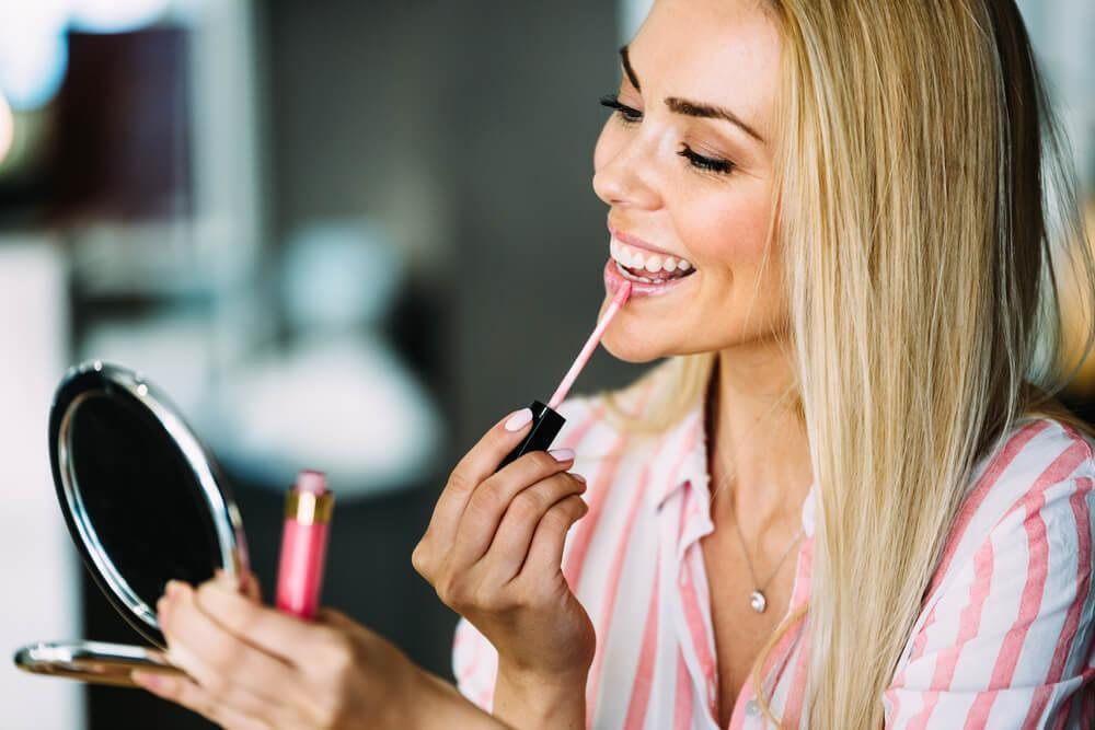 Woman applying lip gloss