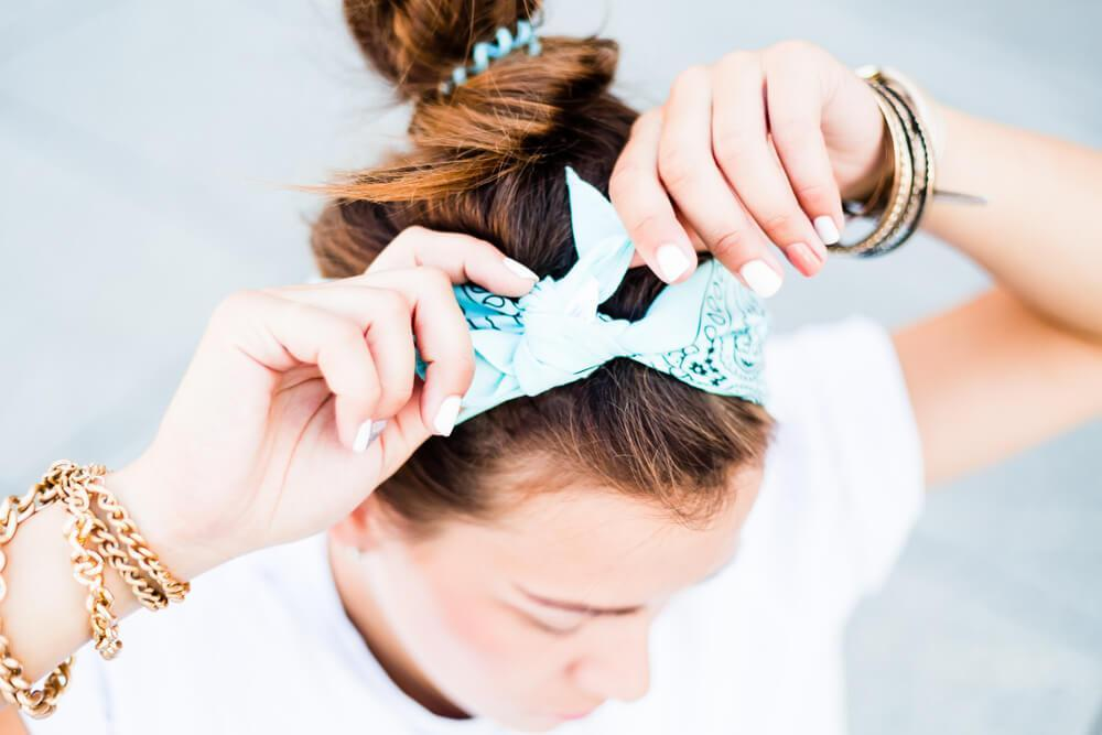 Young woman tying up a hair bow on top of head