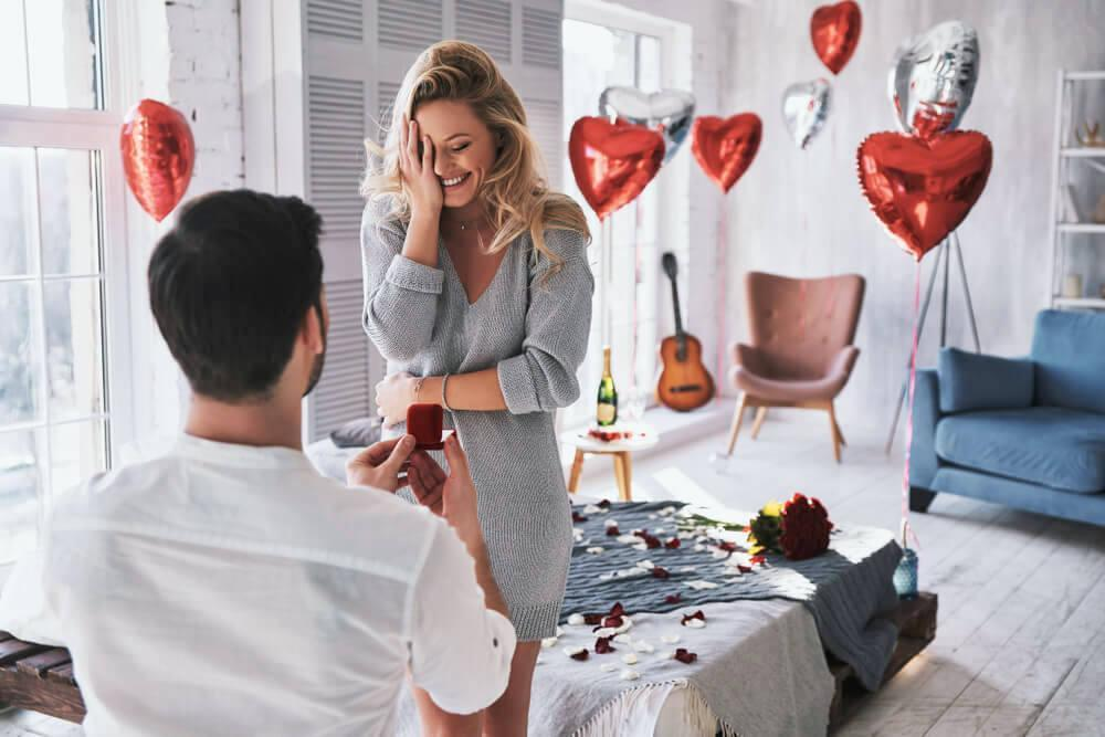 Man proposing to girlfriend in room, with heart-shaped balloons