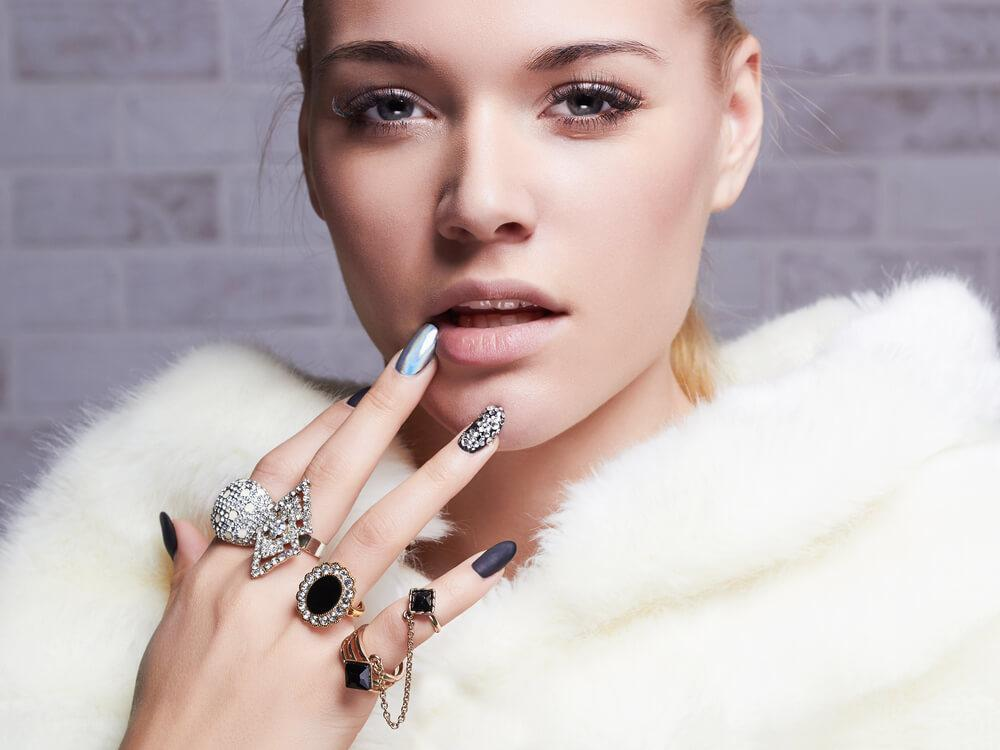 Fashionabel woman in white fur collar, with multiple rings and fashionable silver nail art