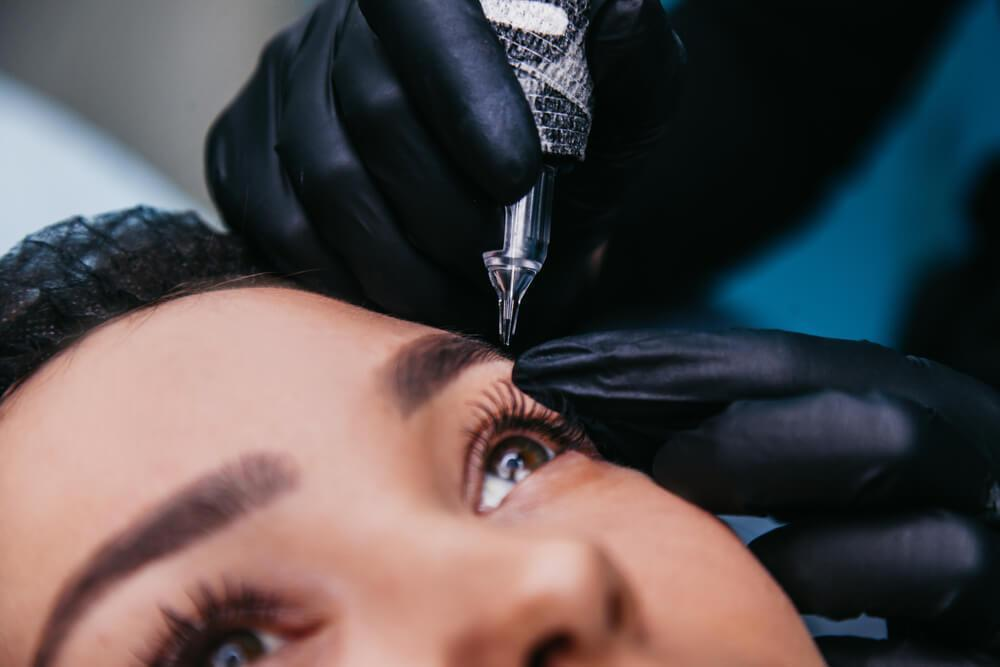 Woman having eyebrow tattoo done